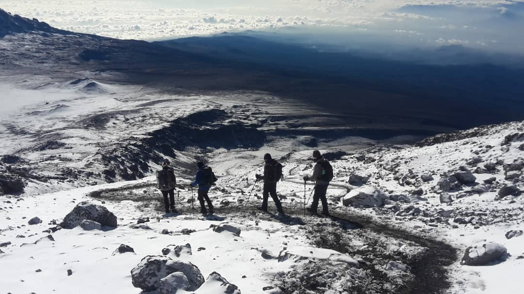 Trekkers Descending Barafu Ridge in Snow